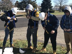 CCTP Students put on personal fall arrest kits provided by Wimsatt Building Materials