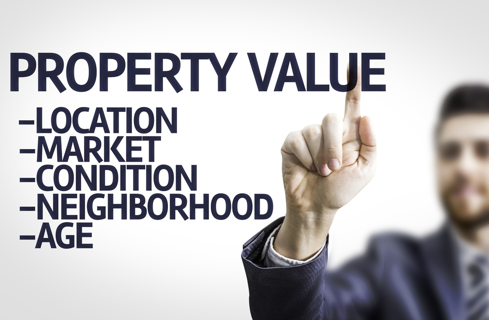 Business man pointing to transparent board with text Property Value