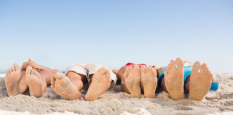 Feet of friends lying together on the beach.jpeg