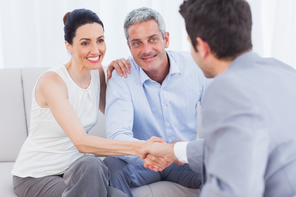 Woman shaking hands with salesman sitting beside husband on couch at home